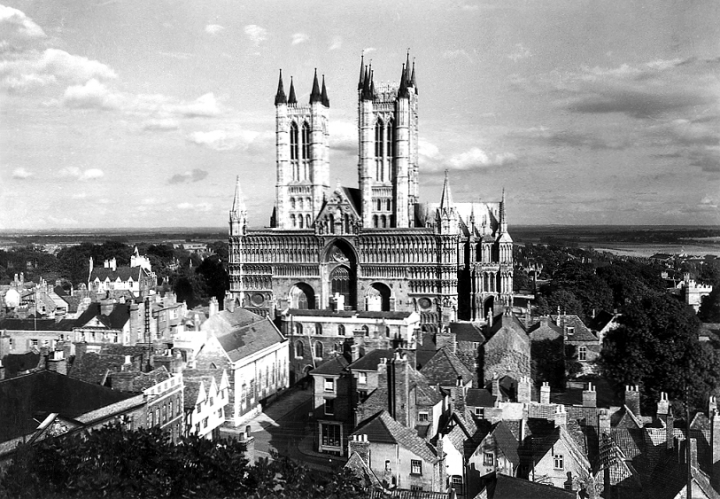 A wide shot of Lincoln Cathedral from the front and the surrounding landscape, with houses in the foreground and flat countryside in the background. The photo is from the 1930s (catalogue reference INF 9/699).