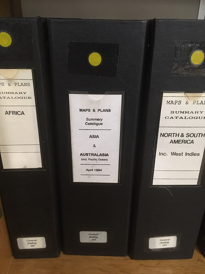 The spines of three wide folders lined up on a bookcase: three volumes of our 'Summary Catalogues', located in the Map and Large Document Reading Room at The National Archives in Kew.