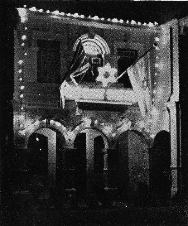 A black and white photo of a colonial building, actually a synagogue, with two flags hanging from an upper balcony, one British, the other carrying the Star of David.